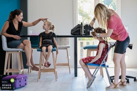 Photographie de mariage d'Annecy alors que maman caresse sa fille, tandis que son autre fille se fait coiffer