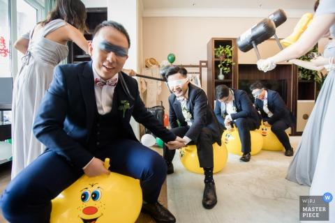 Fotografia di matrimonio da Hangzhou, Cina, degli uomini dello sposo che si schiantano contro il cancello e giocano