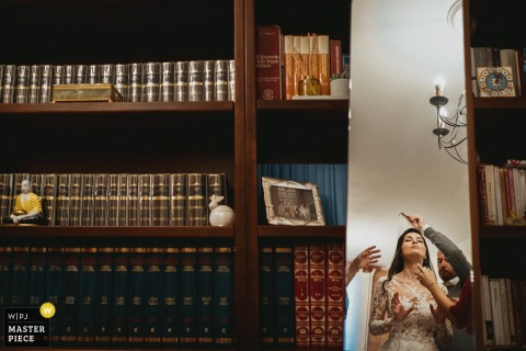Fotografia di matrimonio Roma dalla casa della sposa laziale mentre la sposa si prepara a mettere il velo