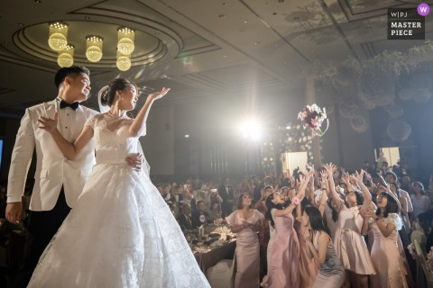 London wedding photographer caught this flower toss image at the Sunee Grand Hotel, Ubon Ratchathani - Bouquet time