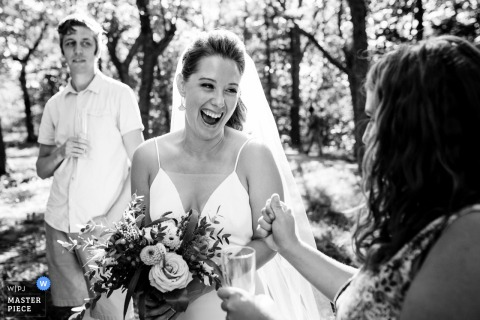 A Quebec wedding photo from Montreal of an Excited bride being congratulated by friend after wedding ceremony in park