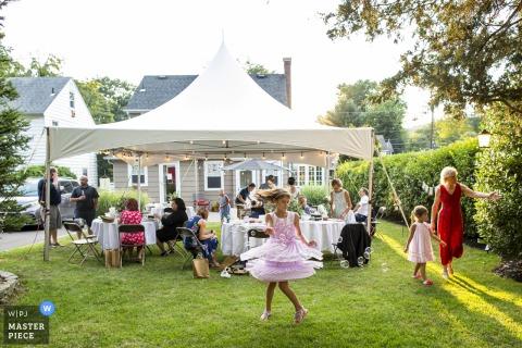 New Jersey Hochzeitsfotografie von einem Hinterhofempfang eines kleinen Mädchens, das sich in Blasen dreht, während die Sonne während einer intimen Hinterhofhochzeit untergeht