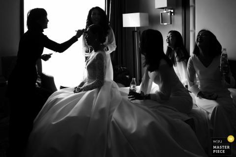 Fotografía de la boda de China en el hotel de Beijing Antes de la ceremonia, la novia se está arreglando el maquillaje y las damas de honor se ríen del juego de recién casarse.