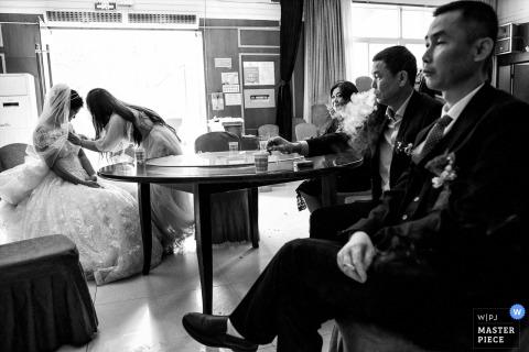Chengdu huwelijksfotografie uit Sichuan van De bruid en haar ouders wachten op het begin van de ceremonie. Aan de linkerkant is de zus van de bruid haar trouwjurk aan het opruimen. Rechts spuugt de vader van de bruid rook uit. In de verte