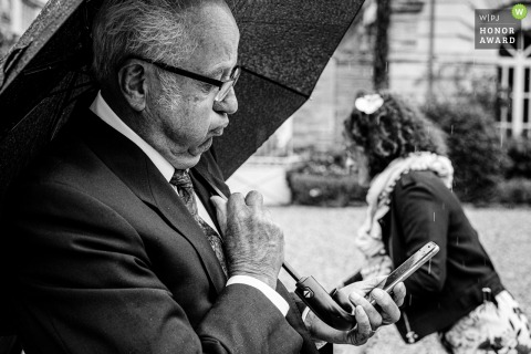 Fotografía de boda lluviosa francesa del Chateau de Conques, Buzet sur Tarn, Francia con un hombre revisando su teléfono en busca de lo que dice el informe meteorológico