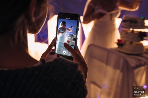 A Lodzkie wedding photographer created this image at the Monastery of the Bernardine Fathers in Piotrkow Trybunalski, Poland - A shot over the shoulder of the wedding guest's phone filming the bride cutting a cake