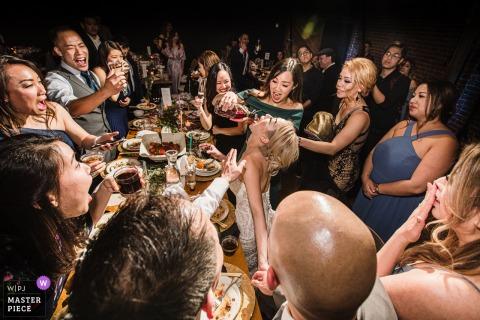 Foto di matrimonio in California da San Jose di ospiti che restituiscono il favore acquistano colpi di cognac alla sposa. Questo matrimonio è stato l'ultimo scatto di nozze prima della chiusura della pandemia