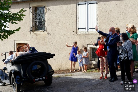 Occitanie wedding photography at the Calvignac in the Lot showing the Departure of the bride and groom in a vintage car, to the cocktail party - Bride and groom and guests wave their hands in farewell