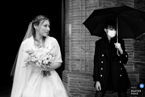 Wedding photography from Pibrac in Haute-Garonne in Occitanie of the Church exit of the bride - Contrast between her white dress and the black outfit of her witness. One in white without mask and umbrella, the other with white mask, dressed in black