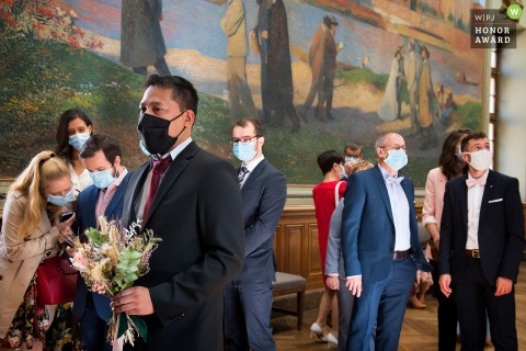 Wedding photo from Toulouse Town Hall in Haute-Garonne Occitanie In the room, guests are chatting, looking around, and a group is looking at a picture on a cell phone. On the large painting, the characters do the same but are reading a book