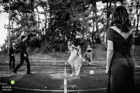 Ancona outdoor wedding photo of some bride and groom football / soccer action on the field