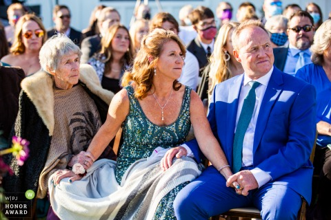 Foto di matrimonio cerimonia all'aperto in Colorado da The Woodlands, Morrison che mostra i membri della famiglia che si tengono per mano mentre guardano la cerimonia