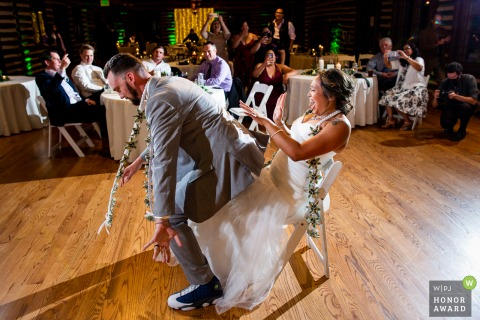 Colorado wedding photography from Hudson Gardens, Denver showing The bride plays the drums on her new husband's booty at the reception