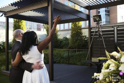 Een huwelijksfoto in Massachusetts met een bruid en bruidegom uit Cambridge, MA die hallo zeggen tegen de gasten van Zoom