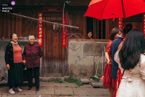 Een trouwfotograaf uit Fujian legde toeschouwers vast die toekeken terwijl de bruid en bruidegom onder een rode paraplu door de straten liepen