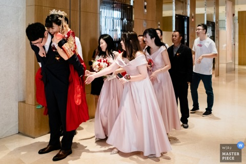 一位北京婚礼摄影师向我们展示了一张载着新娘带去婚礼车上的新郎的照片-因为衣服太滑,新娘就要掉下来了。 伴娘赶紧帮助新郎抱新娘
