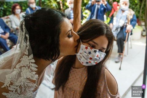 Fotografia di matrimonio in Turchia da Gaziemir che mostra un bacio d'addio durante la tradizionale cerimonia di ricevimento della sposa turca