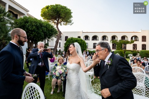 Outdoor garden wedding photo from Grand Hotel Baia Verde, Aci Castello with the The elegant gesture of the father who hands over his daughter to the future husband