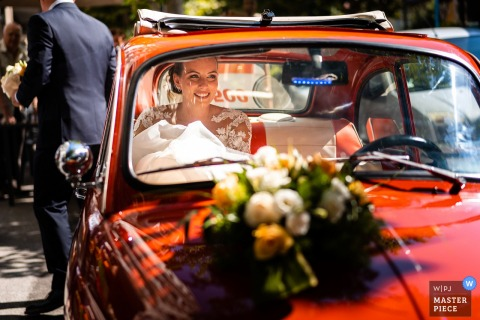 Trieste wedding photo from Italy showing the happy Bride in the red car