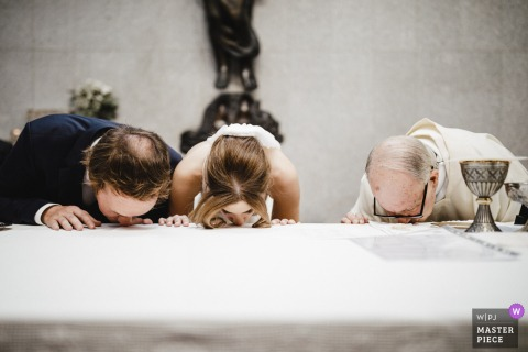 Porto - Portugal wedding photography of the couple and the priest kissing at the church table