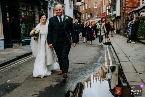 Immagine del matrimonio degli sposi che camminano felici per le strade di York, con la cattedrale riflessa in una pozzanghera