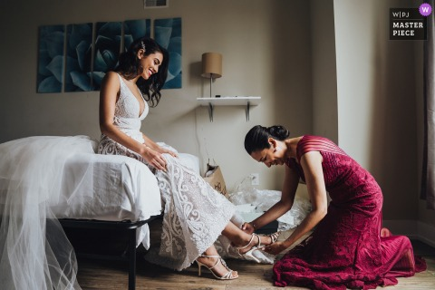 Virginia wedding photography from Arlington showing Mom helping the bride getting ready with her shoes