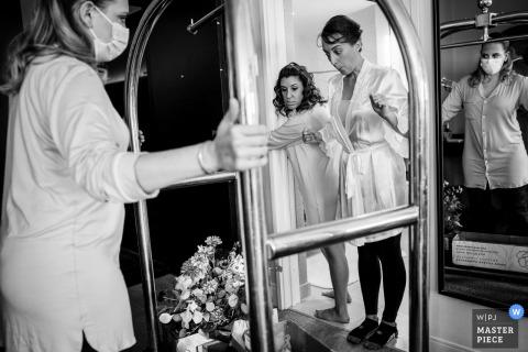 Pennsylvania Hochzeitsfotografie der Braut, die ihre Blumen zum ersten Mal an dem Tag sieht, während ihre Brautjungfern sie in das Hotelzimmer rollen