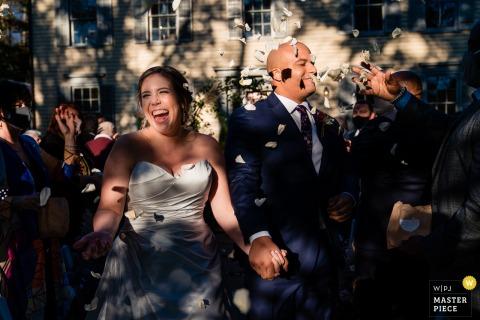 Outdoor PA Hochzeitsfotografie aus Philadelphia des Bräutigams mit Blumen ins Gesicht geworfen, als er und seine heutige Frau die Zeremonie an einem sehr sonnigen Tag verlassen