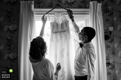 Pennsylvania wedding photo from the Hotel during Prep as the Groom is helping the bride get the dress down from where she hung it up when the checked into their bed and breakfast for their elopement