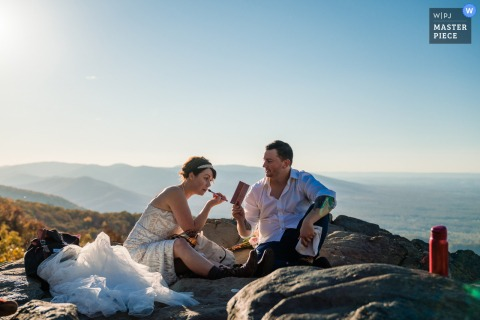 Pennsylvania wedding photographer created this image of a Philadelphia Ceremony	of the Groom helping his bride touch up her makeup after the hike up to the top of this mountain for their elopement ceremony