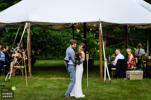 VT outdoor, tented wedding photo from Manchester, Vermont as The bride and groom share their first dance with their dog