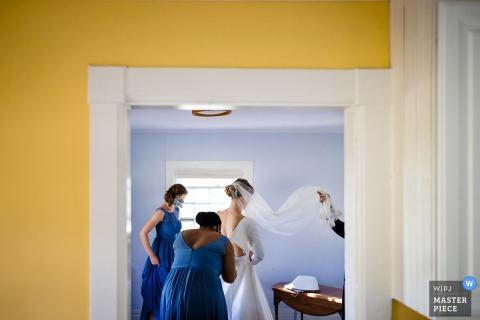 Trouwfotografie in Vermont van het klaarmaken bij Shelburne Farms, VT - De bruid maakt zich klaar met wat hulp van haar bruidsmeisjes