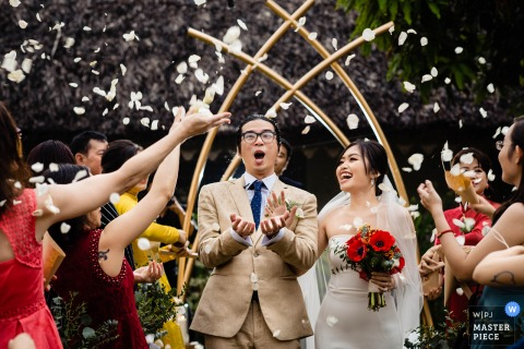 Vietnam wedding Ceremony photography of the bride and groom exiting under flying flower petals