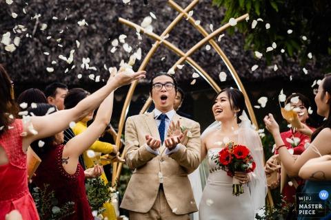 Vietnam cerimonia di matrimonio fotografia della sposa e dello sposo che escono sotto petali di fiori volanti