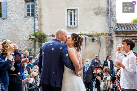 An Ardeche wedding photographer captured this Auvergne-Rhône-Alpes Couple Kiss in front of the church