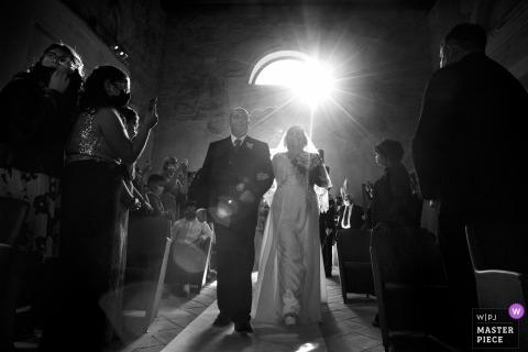 Der Hochzeitsfotograf von Reggio Calabria schuf dieses Bild in der alten Kirche von Carafa Castle in Roccella Jonica, Italien, das den Eintritt der Braut in die Kirche zeigt