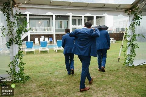 Fotografia di matrimonio all'aperto nella Carolina del Nord di Beach King, Nags Head mentre lo sposo e i testimoni si preparano a correre sotto la pioggia in un giorno di nozze piovoso