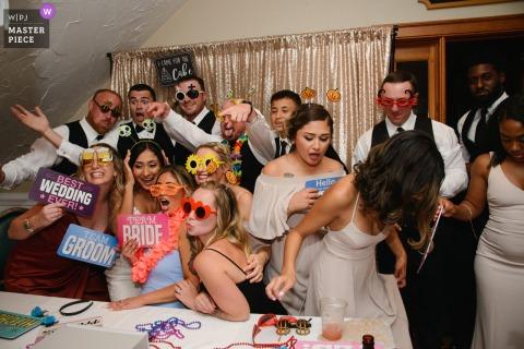 Photographie de mariage en Caroline du Nord du Currituck Club, Corolla, Caroline du Nord, d'un verre renversé pendant que les membres de la fête de mariage prennent une photo amusante