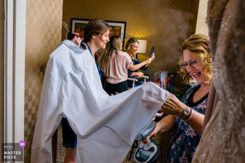 Fotografo di matrimoni MD che scatta foto al Belvedere, Baltimora di La madre della sposa che fuma una camicia bianca mentre le ragazze si truccano