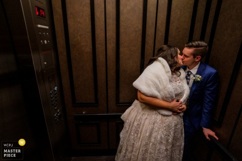 MD wedding photography from Hotel Monaco, Baltimore as The couple kiss in the elevator at the end of the night