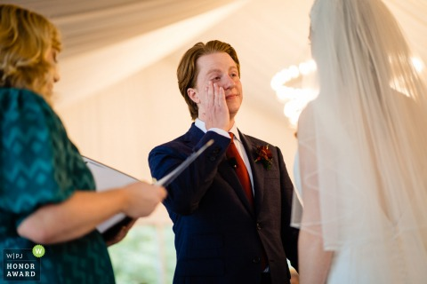Georgia indoor wedding photography from the Atlanta ceremony as the groom is wiping away the tears