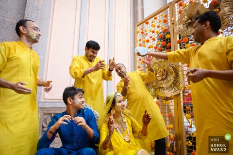 Tradities huwelijksfotografie van de Haldi-ceremonie op de trouwdag in Emirates Palace, Abu Dhabi van de broers The bruiden die met elkaar genieten van de bruiloft van hun kleine zusje