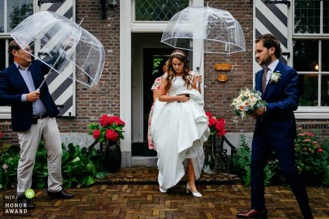 Photographie de mariage en plein air de la mariée marchant dehors sous la pluie avec l'aide des hommes et des parapluies clairs