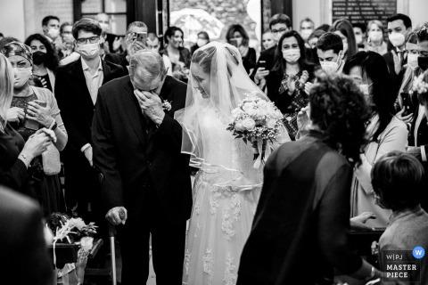 Il fotografo di matrimoni Verbano-Cusio-Ossola ha catturato questa immagine della cerimonia della chiesa piemontese de L'arrivo della sposa con suo nonno