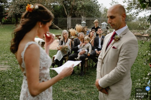 Rio Grande do Sul outdoor ceremony wedding photo at the grooms house	showing the Father of the bride asking the child to be silent