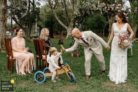 Fotografo di matrimoni del Rio Grande do Sul che scatta foto durante una cerimonia nel cortile della casa degli sposi dello sposo che saluta suo figlio