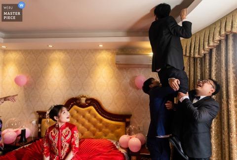 Le photographe de mariage Jinhua a capturé cette image amusante au domicile de la mariée du Zhejiang des meilleurs hommes à la recherche des chaussures de mariage de la mariée