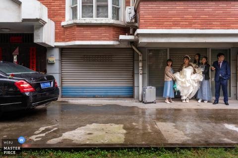 Photographie de mariage Jinhua du Zhejiang chez le marié du couple en attente de voiture pour aller à l'hôtel