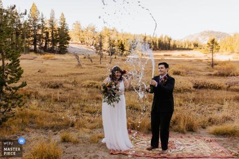 Fotografía de boda después de una ceremonia al aire libre en New Washoe City, NV de La novia y el novio sorprendidos por la explosión de champán debido al cambio de altitud