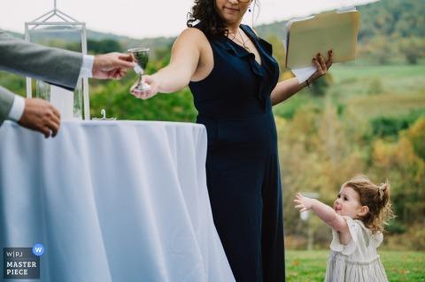 Il fotografo di matrimoni del Distretto di Columbia ha catturato questa immagine presso The Inn at Mount Vernon Farm, Sperryville, Virginia, di una piccola fioraia che chiede un bicchiere di vino durante la cerimonia ebraica